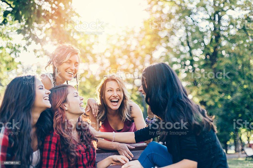 Teenage girls storytelling in  the park stock photo