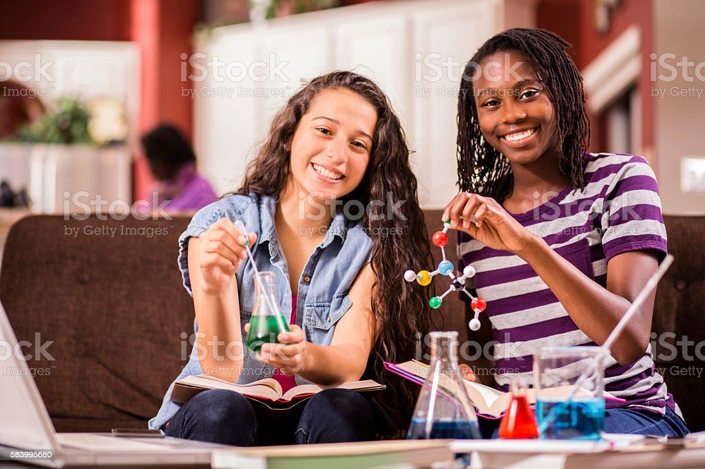 Teenage girls, students studying chemistry, science at home. stock photo