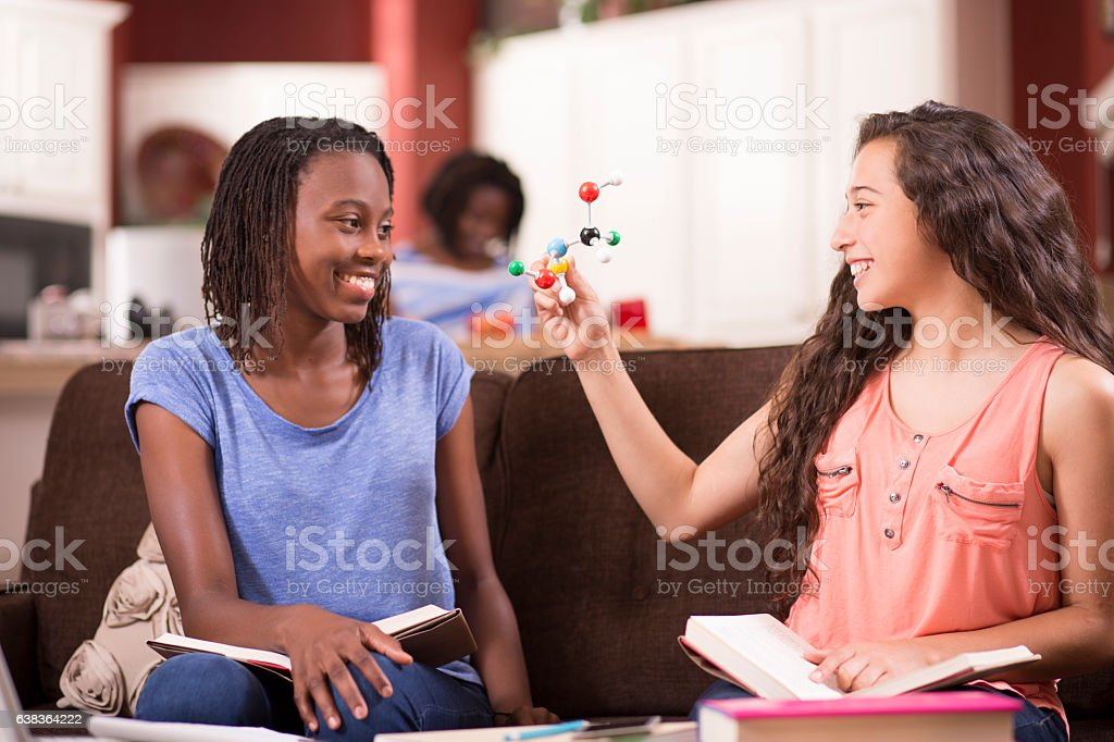 Teenage girls studying DNA molecule, science at home. stock photo