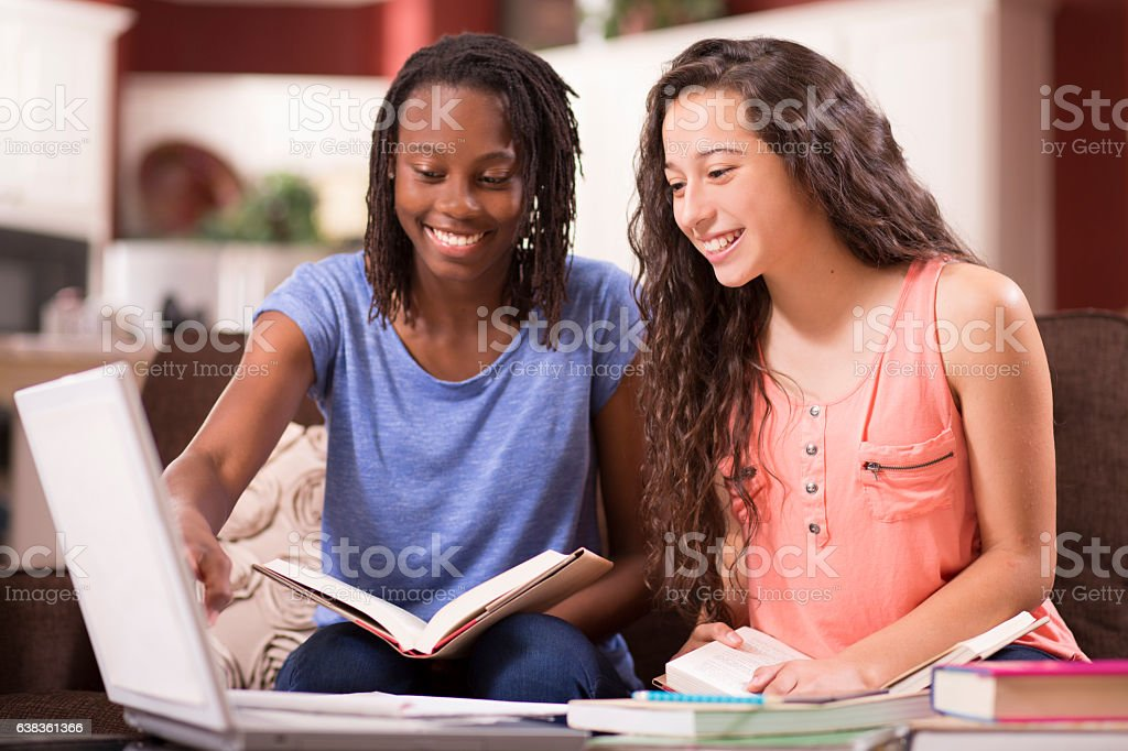 Teenage girls studying, doing homework at home. stock photo