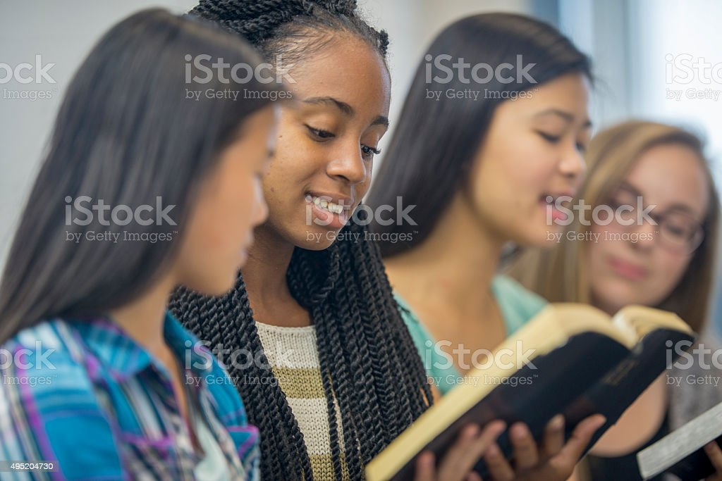Teenage Girls Studying the Bible Together stock photo