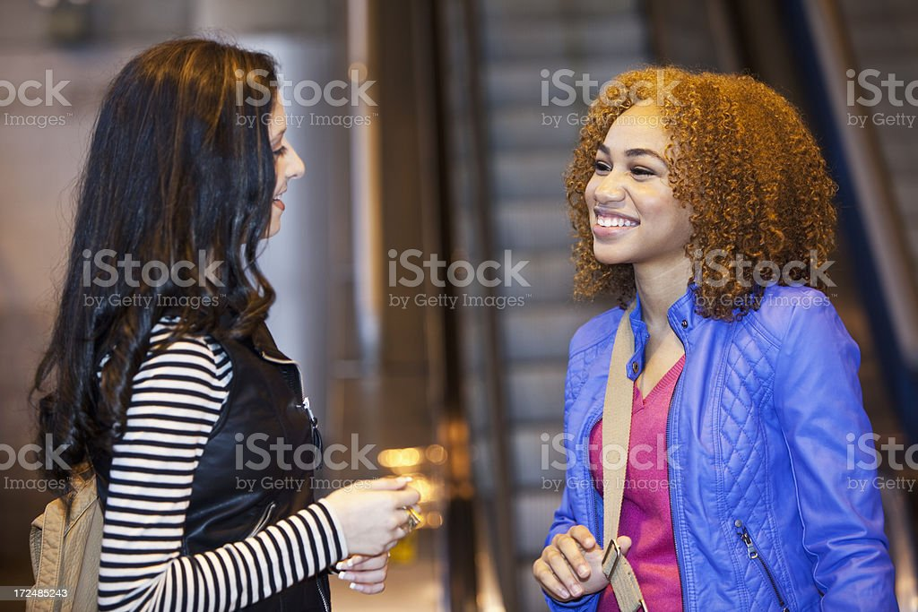 Teenage girls talking at bottom of escalator stock photo