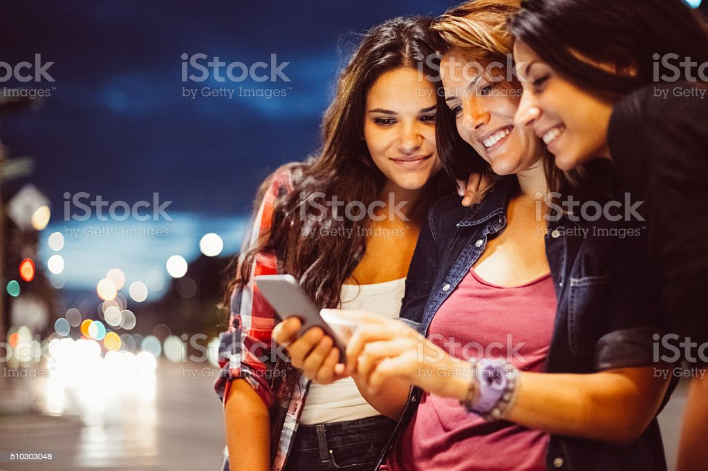 Teenage girls texting for Uber stock photo