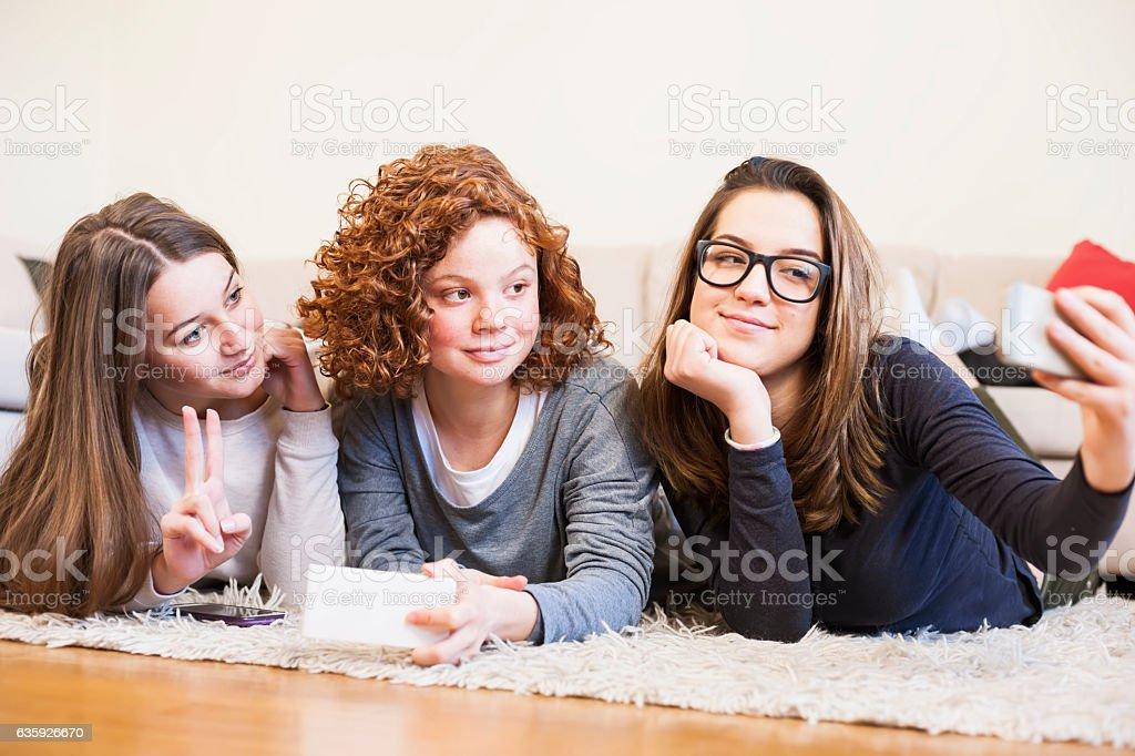 Teenage girls using smart phones stock photo