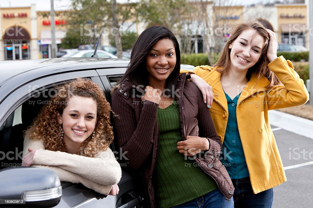 Teenage girls with car, in parking lot stock photo