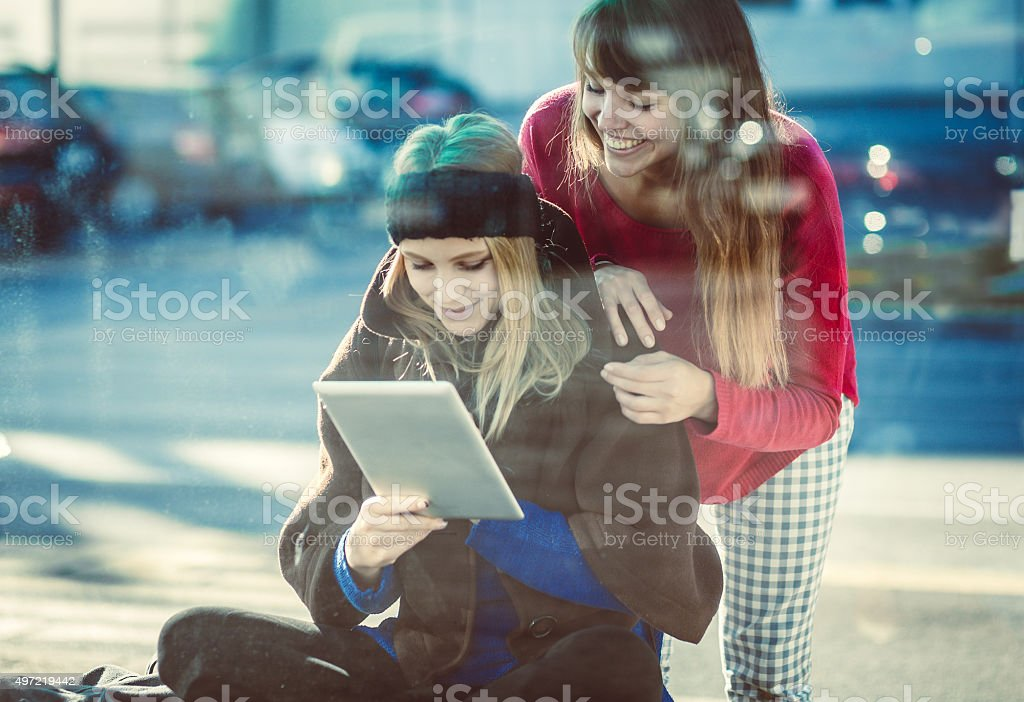 Teenage girls with digital tablet on the bus station stock photo