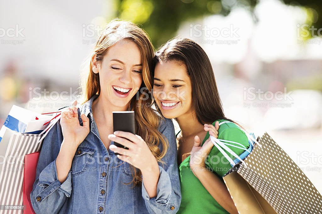 Teenage Girls With Shopping Bags Reading Text Message royalty-free stock photo