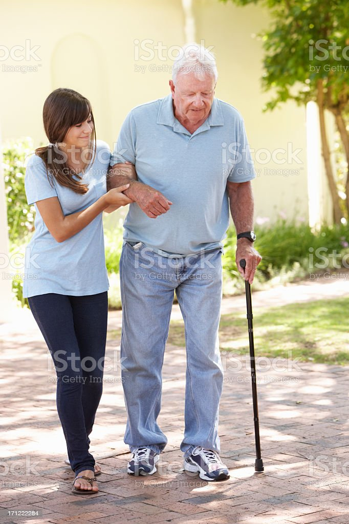 Teenage Granddaughter Helping Grandfather Out On Walk stock photo