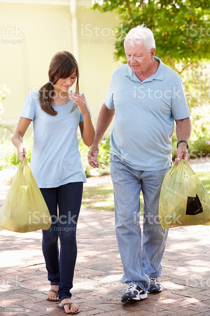 Teenage Granddaughter Helping Grandfather With Shopping royalty-free stock photo