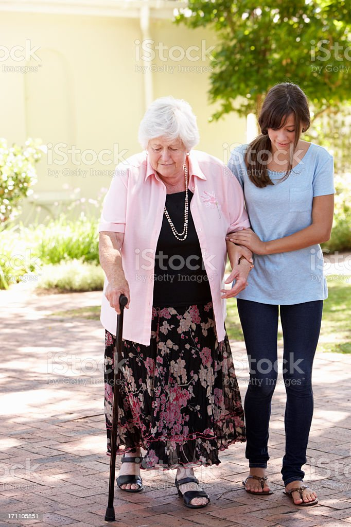 Teenage Granddaughter Helping Grandmother Out On Walk royalty-free stock photo