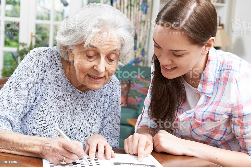 Teenage Granddaughter Helping Grandmother With Crossword Puzzle stock photo