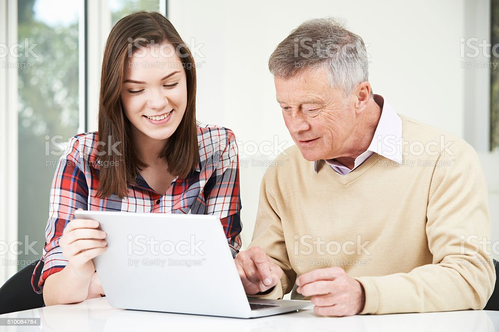 Teenage Granddaughter Showing Grandfather How To Use Laptop Comp stock photo