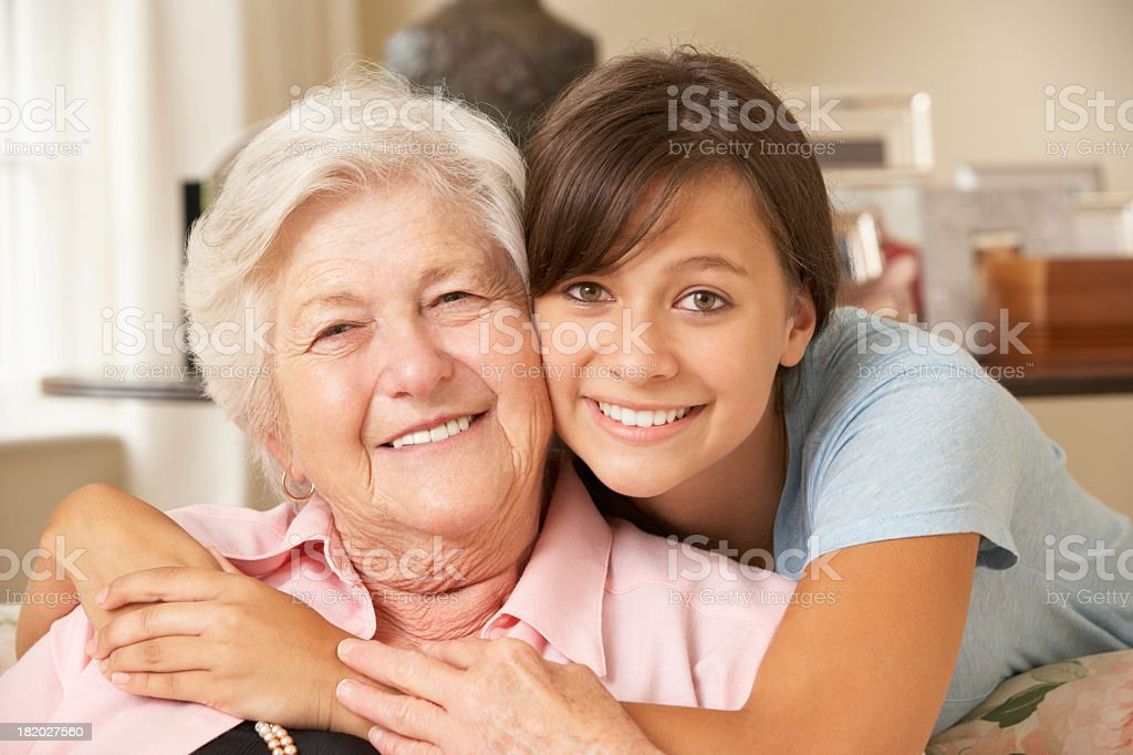 Teenage Granddaughter Visiting Grandmother At Home stock photo