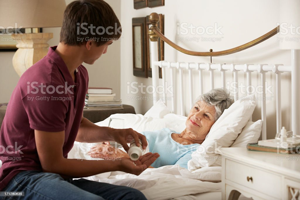 Teenage Grandson Giving Grandmother Medication In Bed stock photo