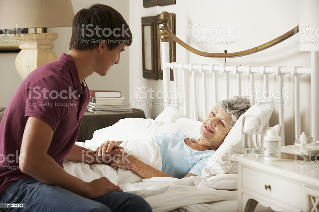 Teenage Grandson Visiting Grandmother In Bed stock photo