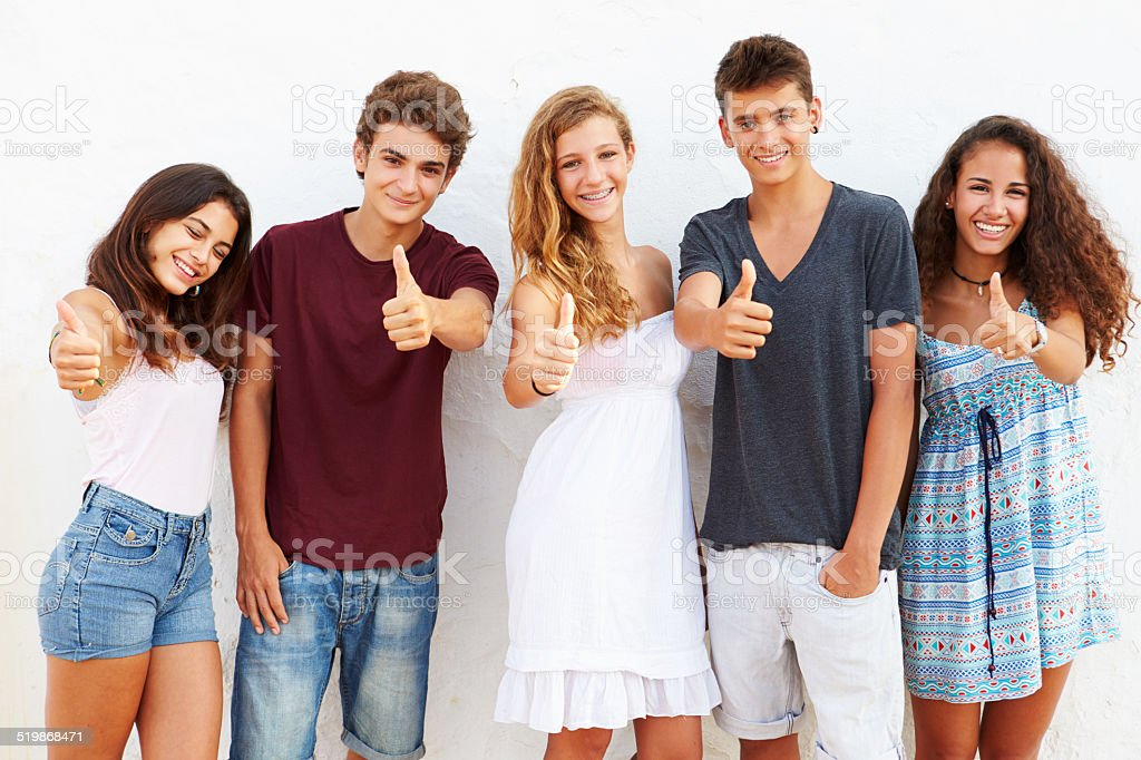 Teenage Group Leaning Against Wall Giving Thumbs Up stock photo