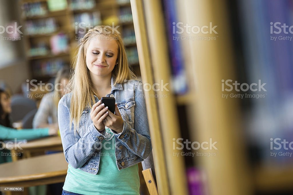 Teenage high school student using smart phone to text royalty-free stock photo