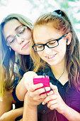 Teenage high-school girls enjoying media on mobile phone