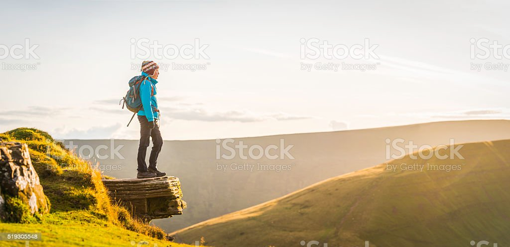 Teenage hiker on mountain top overlooking golden sunset wilderness panorama stock photo