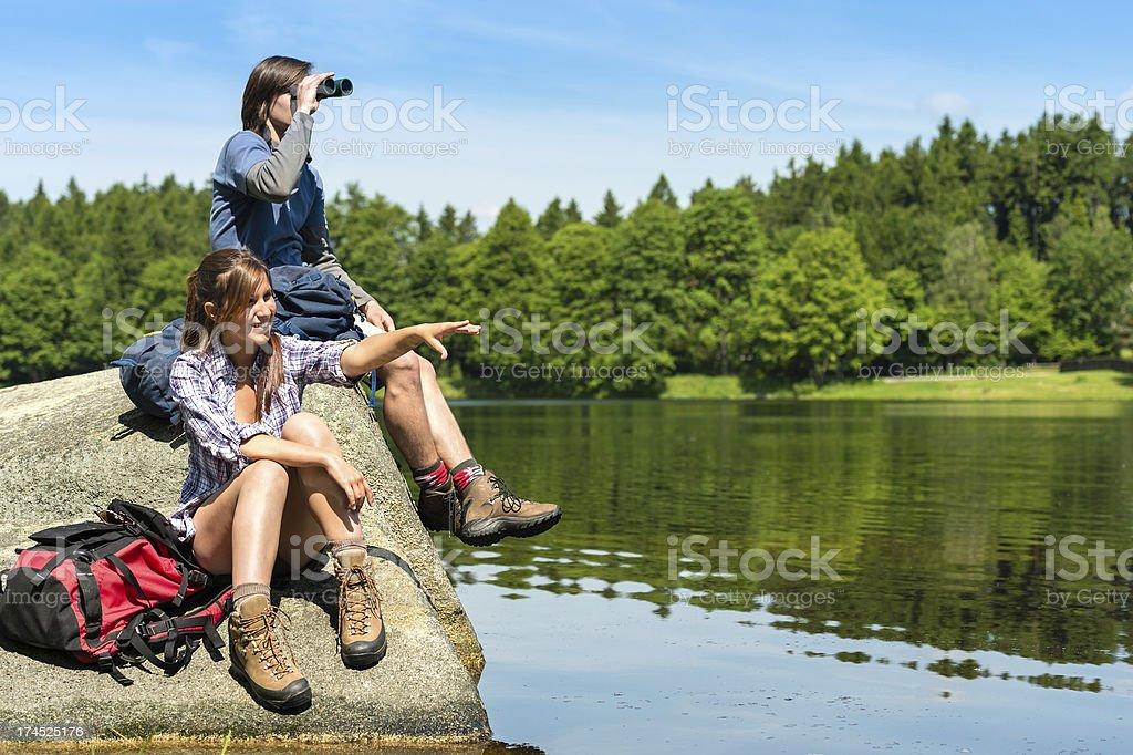 Teenage hikers birdwatching at lake stock photo