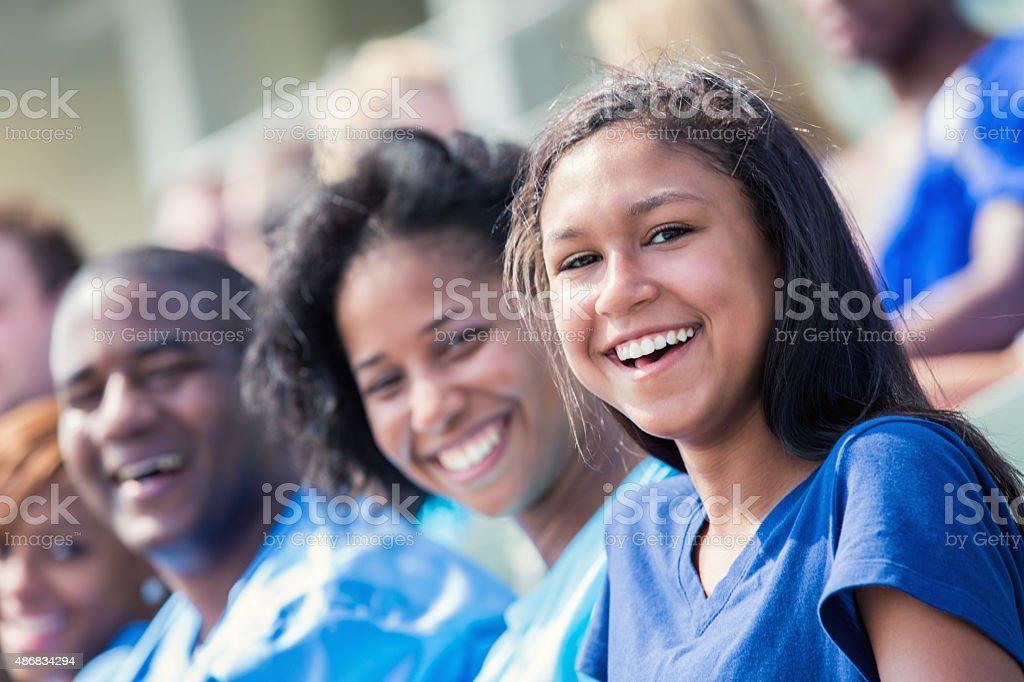 Teenage Hispanic girl in stadium watching sporting event stock photo