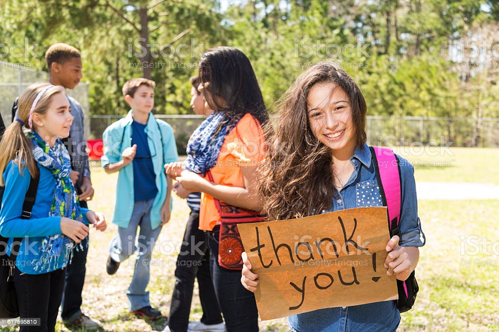 Teenage Latin girl holds 'Thank You' sign in park. stock photo