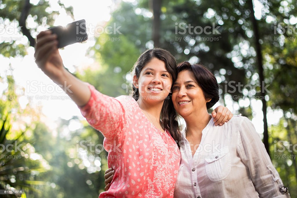 Teenage latin girl taking selfie with her mother stock photo