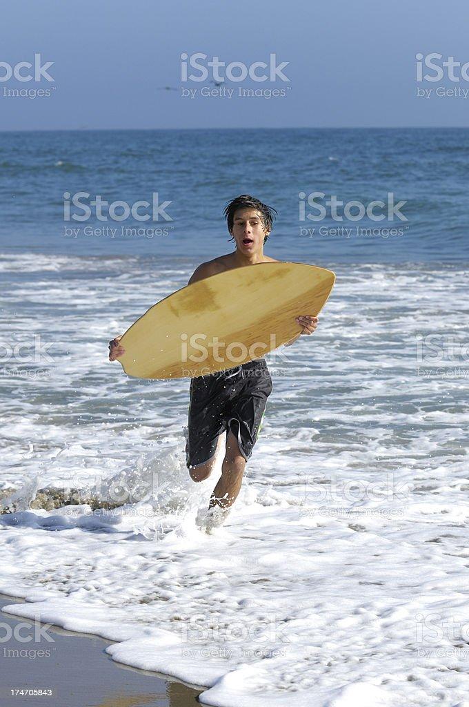 Teenage Latino Boy Skimboarding at Beach royalty-free stock photo