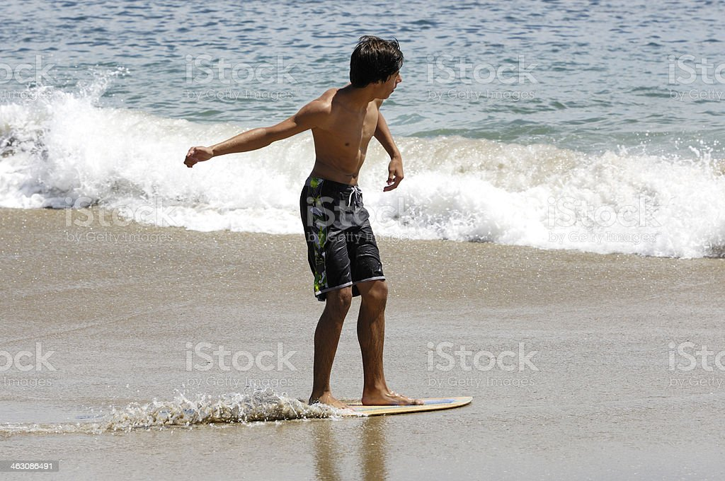 Teenage Latino Boy Skimboarding at Beach stock photo