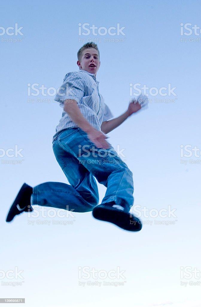 Teenage male jumps skyward royalty-free stock photo