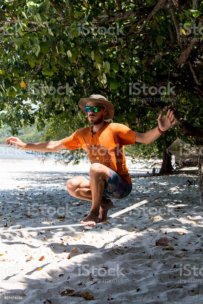 teenage man balancing on slackline stock photo
