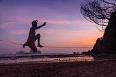 teenage man balancing on slackline with sky view