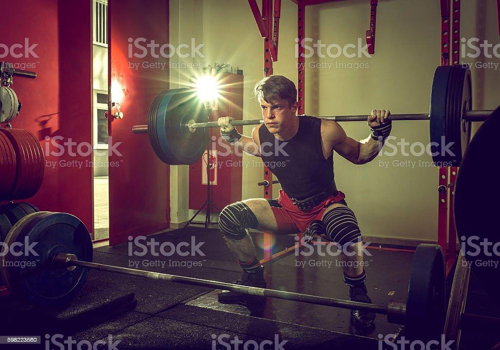 Teenage man doing squats indoor. stock photo