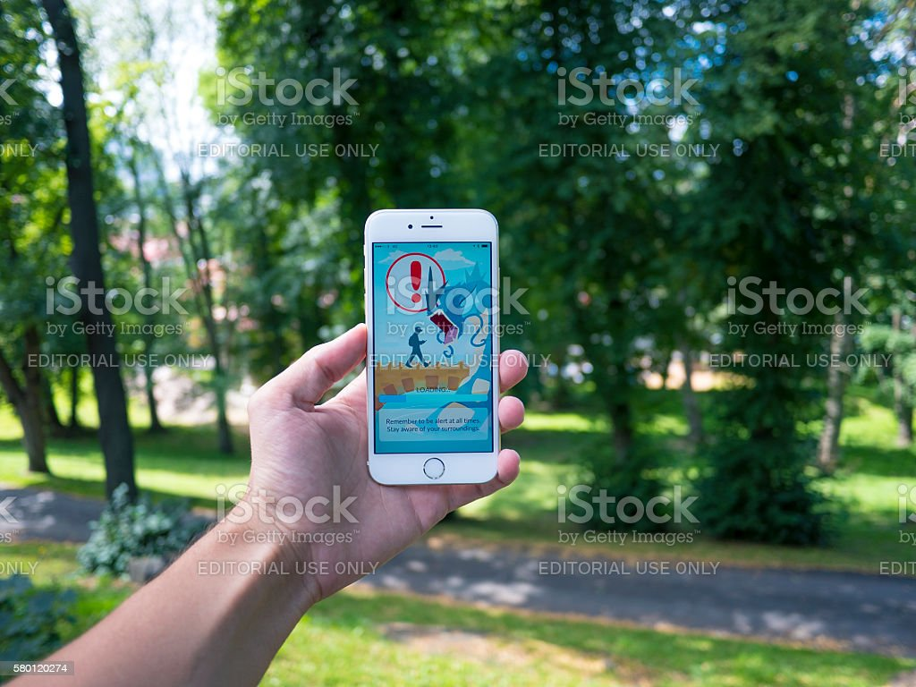 Teenage Man Playing Pokemon GO on a Cellphone stock photo