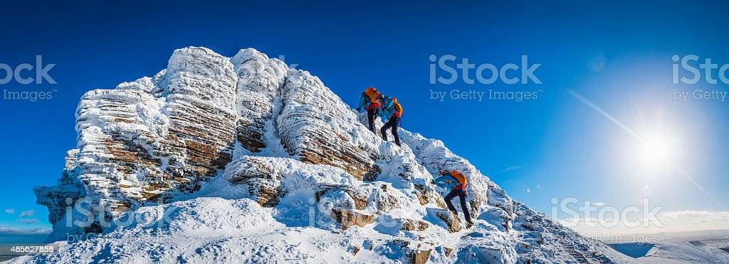 Teenage mountaineer climbing snowy summit multiple exposure panorama winter sunburst stock photo