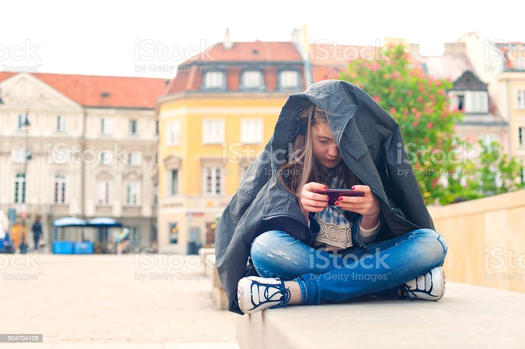 Teenage problems. Young girl addicted to social media technologies. stock photo