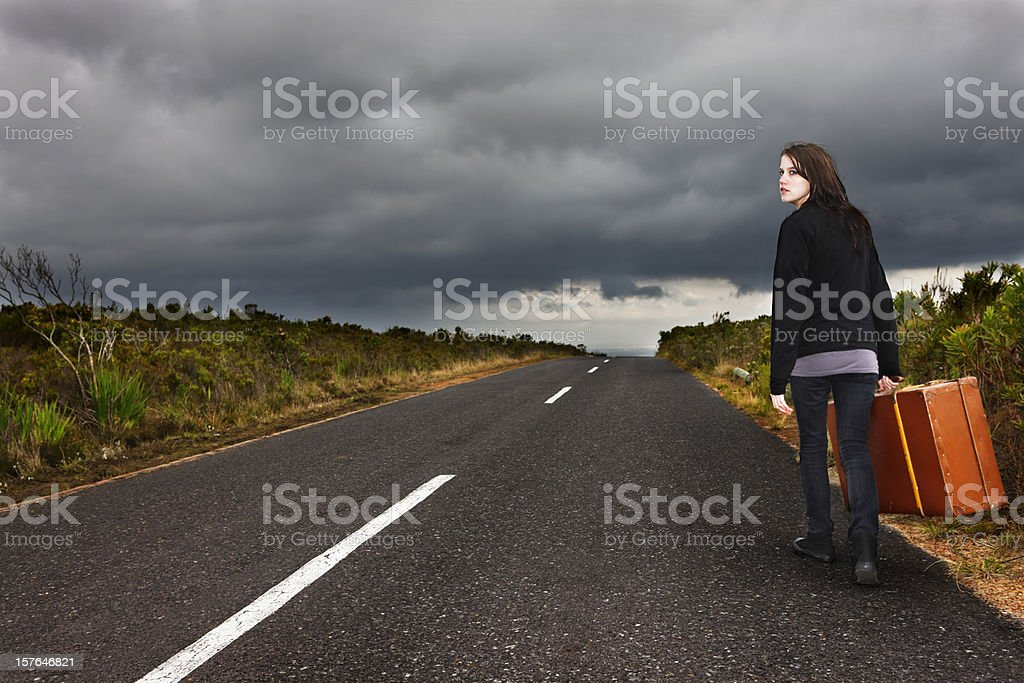 Teenage runaway walks with case beside deserted road at twilight royalty-free stock photo