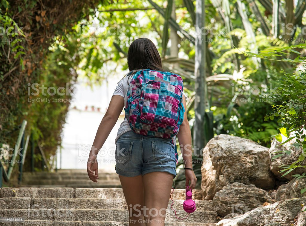 Teenage school girl with a backpack and headphones stock photo
