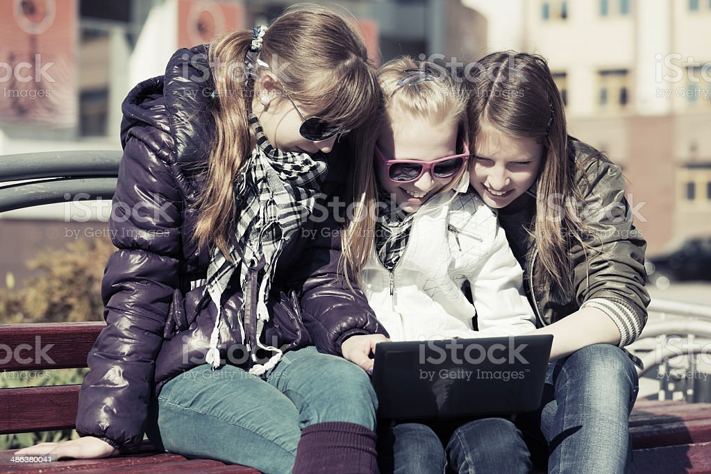 Teenage school girls using laptop on the bench royalty-free stock photo