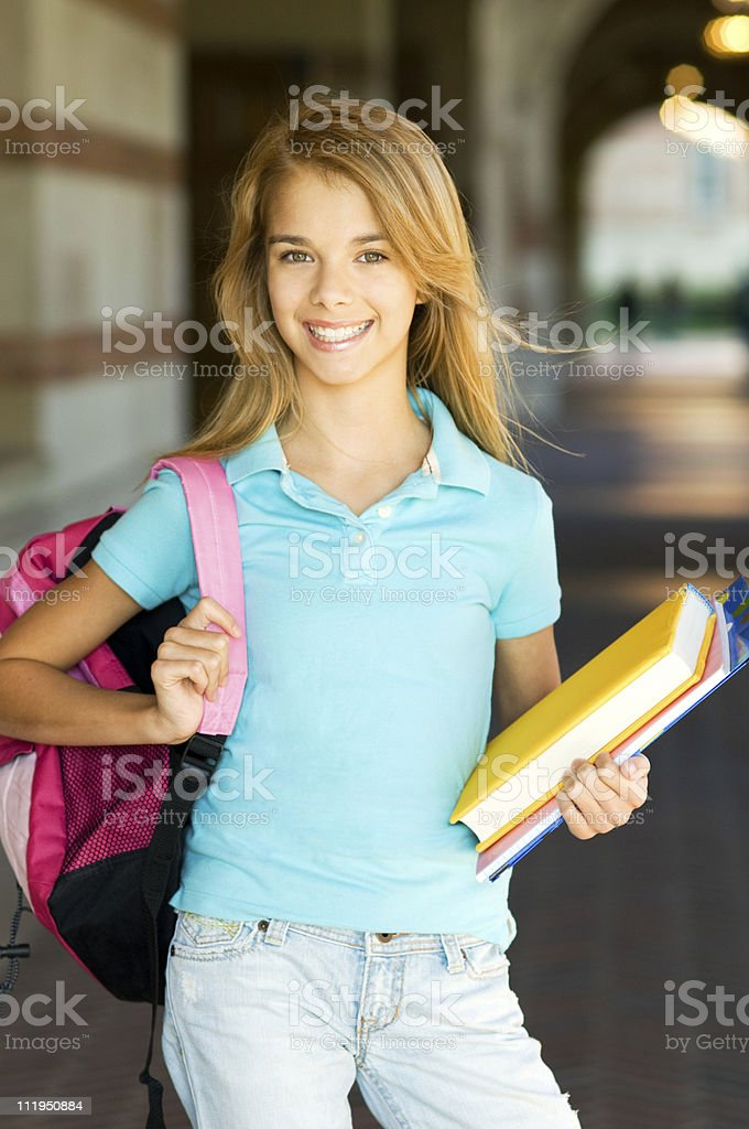 Teenage Schoolgirl holding Books and backpack on campus royalty-free stock photo