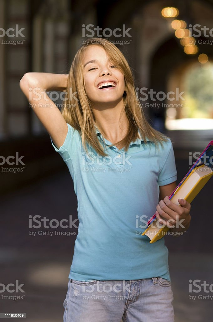 Teenage Schoolgirl Laughing Holding Books on Campus royalty-free stock photo