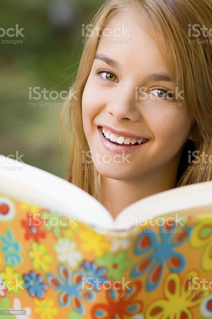 Teenage Schoolgirl Looks up from Reading Textbook with Smile royalty-free stock photo