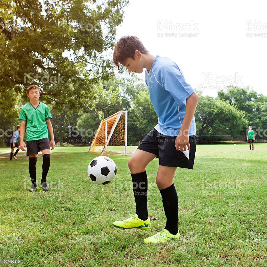 Teenage soccer athlete does tricks with ball stock photo