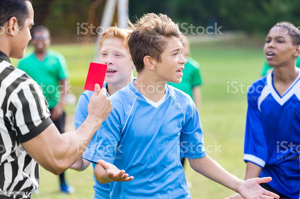 Teenage soccer player objects to referee's penalty call stock photo