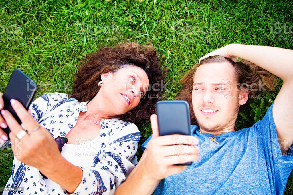 Teenage son unimpressed at mother handling mobile phone stock photo