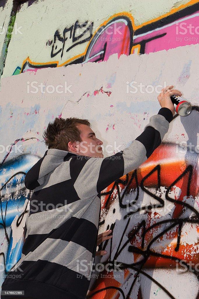 Teenage spray painter painting colorful graffiti stock photo