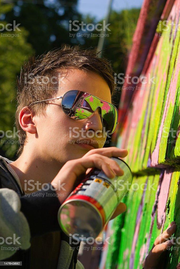Teenage spray painter with sunglasses painting colorful graffiti onto wall royalty-free stock photo