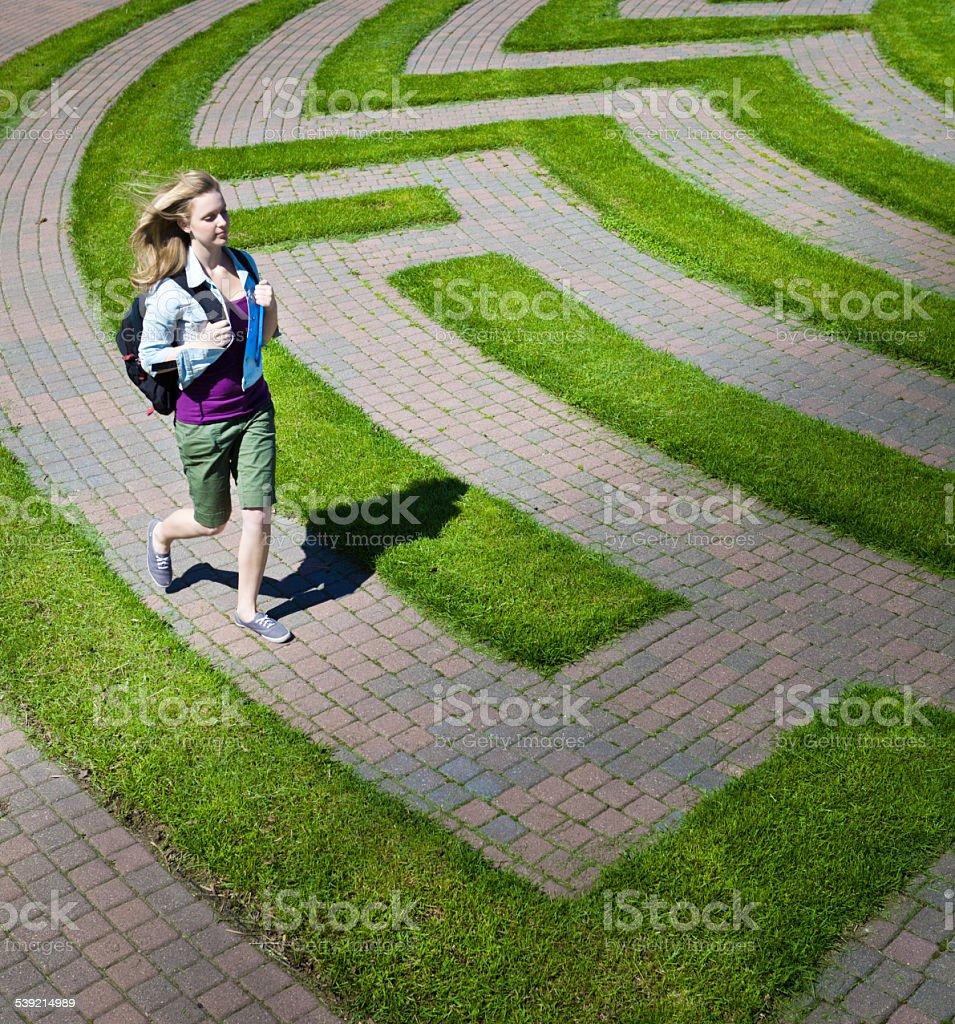 Teenage Student Running in the Maze of College Education stock photo