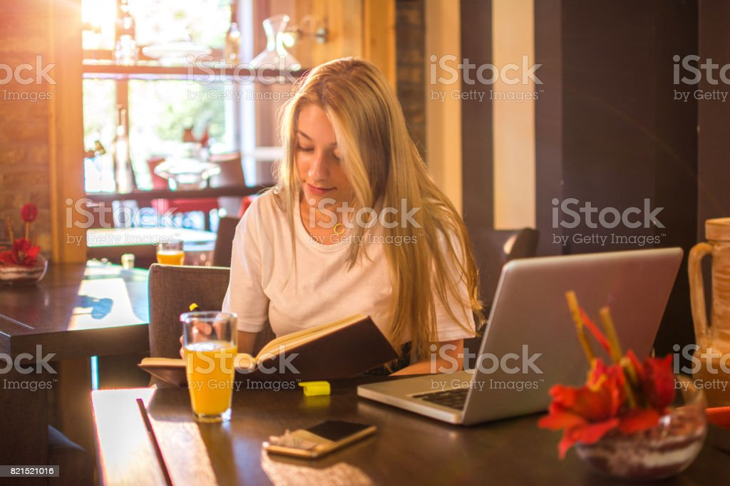 Teenage student with book and laptop preparing for exam at cafe bar.