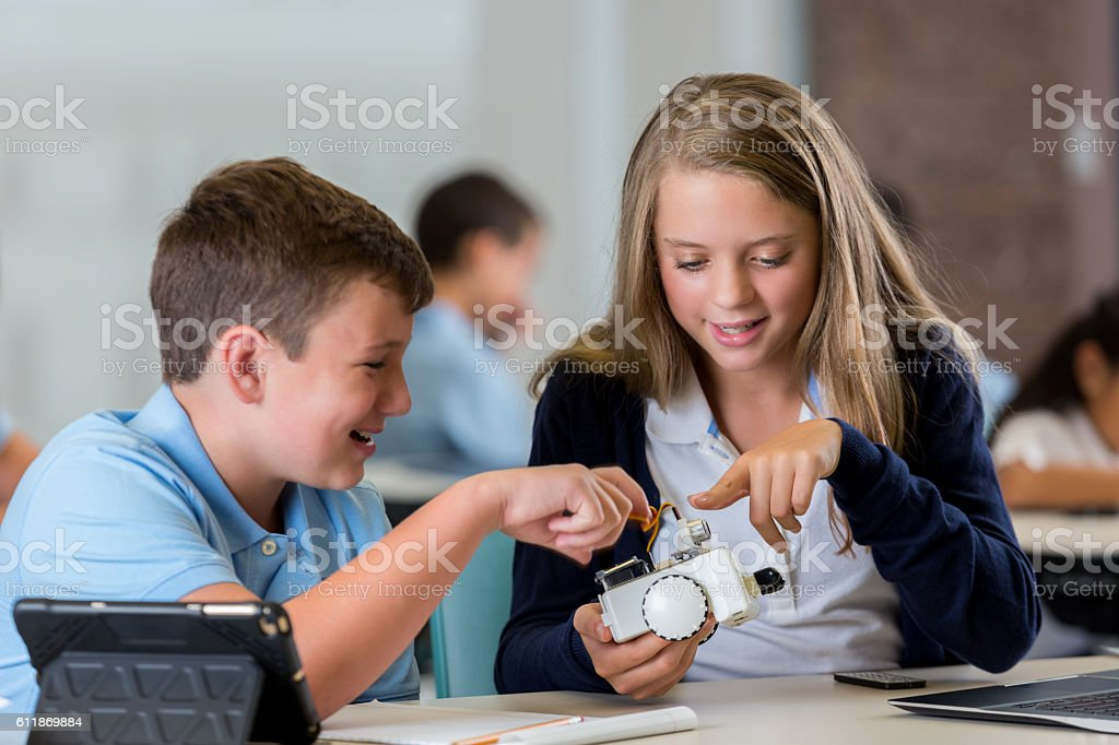 Teenage students build robot together in engineering class stock photo